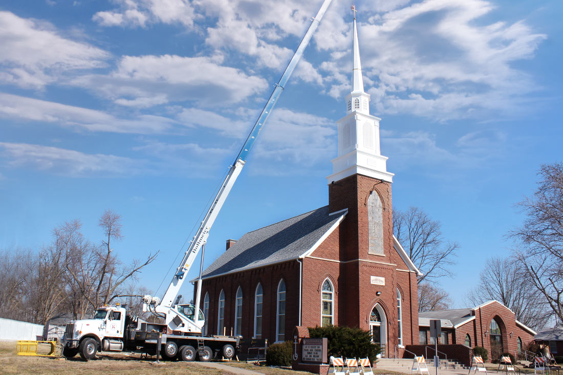 Crane placing cross on the steeple